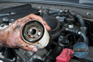 An Auto Mechanic is Holding an Old, Dirty Engine Oil Filter