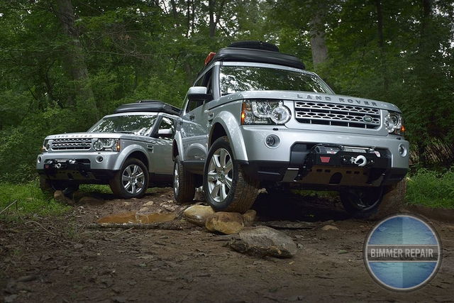 Silver Land Rovers Parked in a Forest.