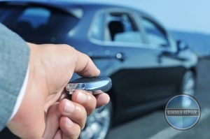 Man Pointing a Programmable Key Fob at a Car.